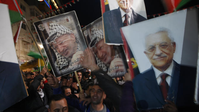 Palestinians celebrate as they wave posters of former Palestinian leader Yasser Arafat, left, and President Mahmoud Abbas, right, as they watch the U.N. General Assembly votes on a resolution to upgrade the status of the Palestinian Authority to a nonmember observer state, in the west bank city of Ramallah, Thursday, Nov. 29, 2012.  The U.N. General Assembly has voted by a more than two-thirds majority to recognize the state of Palestine. The resolution upgrading the Palestinians' status to a nonmember observer state at the United Nations was approved by the 193-member world body late Thursday by a vote of 138-9 with 41 abstentions. (AP Photo/Majdi Mohammed)