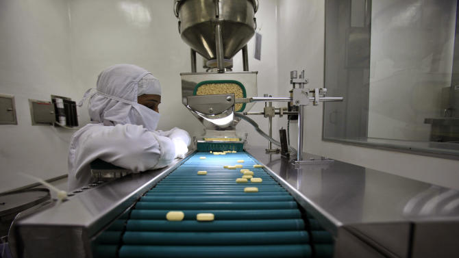 FILE - In this file photo taken Thursday, Feb. 9, 2012, a pharmacist is seen working in a lab where medicines are being produced at a manufacturing unit on the outskirts of Mumbai, India. India's patent office on Monday march 12, 2012  effectively ended Bayer's monopoly on a patented cancer drug by allowing the manufacturing of a generic copy at a fraction of the price. (AP Photo/Rafiq Maqbool, File)