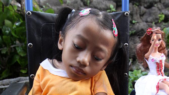 In this April 22, 2012 photo, Alit Astini displays Barbie dolls as she sits on a wheel chair outside her house in Songan village, Kintamani, Bali, Indonesia. Astini and her sister Putu Restiti were kept out of school and had no friends. But like children everywhere, they had powerful imaginations. After being given a Barbie doll, they started stitching tiny, intricate outfits for her from their mother's sewing scraps. And in doing so, they created a new world for themselves.  (AP Photo/Firdia Lisnawati)