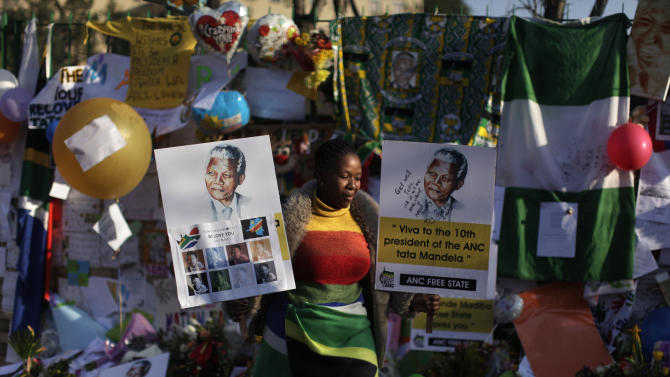 A well wisher holds posters of former South African President Nelson Mandela at the entrance to the Mediclinic Heart Hospital where Mandela is being treated in Pretoria, South Africa, Saturday, June 29, 2013. (AP Photo/Muhammed Muheisen)