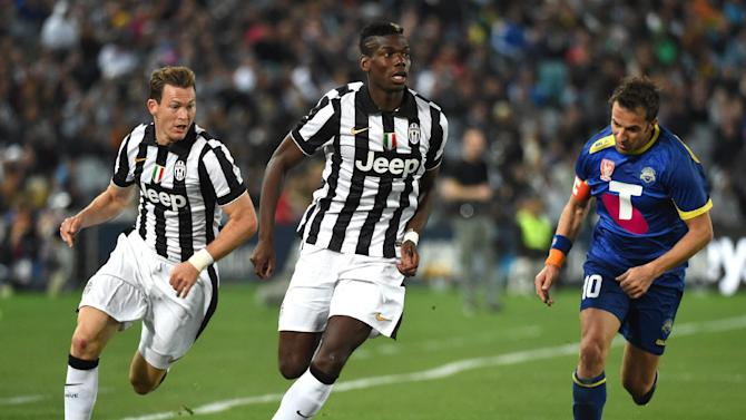 Juventus' midfielder Paul Pogba (centre) runs past Australian All Stars forward Alessandro Del Piero (right) during an exhibition match in Sydney, on August 10, 2014