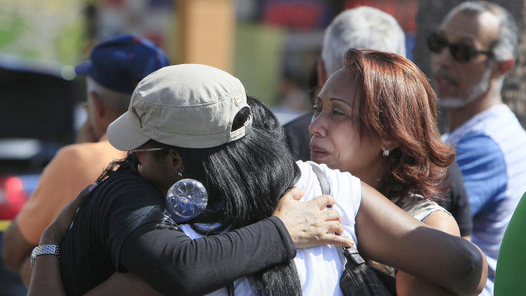 Family and friends gather at the scene of the shooting at Las Dominicanas M&M Hair Salon  Winter Park, Fla., Thursday, Oct. 18, 2012. A gunman opened fire in a central Florida beauty salon Thursday, killing three women and wounding a fourth before killing himself at a nearby home, police said. The shooting appeared to be part of a domestic dispute. (AP Photo/Julie Fletcher)