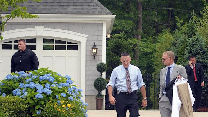 An unidentified attorney of former New England Patriots football player Aaron Hernandez, right, leaves Hernandez's home after securing some dress clothes from the house as police investigators work outside the home Thursday, June 27, 2013, in North Attleboro, Mass. A judge on Thursday denied bail for the former NFL player, who is charged with first-degree murder in the shooting death of a friend. (AP Photo/The Attleboro Sun Chronicle, Mark Stockwell) MAGS OUT. MANDATORY CREDIT, PROVIDENCE JOURNAL OUT
