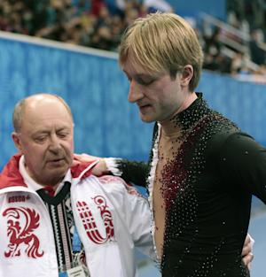 Evgeni Plushenko of Russia, right, and his coach Alexei Mishin leave after Plushenko pulled out of the men's short program figure skating competition due to illness at the Iceberg Skating Palace during the 2014 Winter Olympics, Thursday, Feb. 13, 2014, in Sochi, Russia. (AP Photo/Ivan Sekretarev)