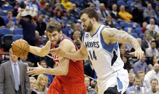 Philadelphia 76ers center Spencer Hawes, left, drives against Minnesota Timberwolves center Nikola Pekovic (14), of Montenegro, during the first quarter of an NBA basketball game in Minneapolis, Wedne