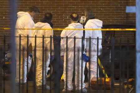 Forensic officers examine scene of shooting where two New York Police officers were shot dead in Brooklyn borough of New York