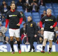 Manchester United's English defender Rio Ferdinand (L) warms up with English midfielder Paul Scholes (R), both wearing the T-shirt from Kick It Out's 'One Game, One Community' campaign before the English Premier League football match between Chelsea and Manchester United at Stamford Bridge in London