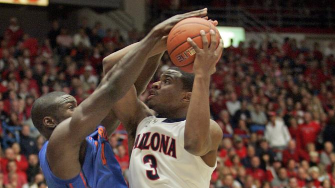 Florida's Patric Young (4) blocks the shot of Arizona's Kevin Parrom (3) during the first half of an NCAA college basketball game  at McKale Center in Tucson, Ariz.,Saturday, Dec. 15, 2012. (AP Photo/John Miller)