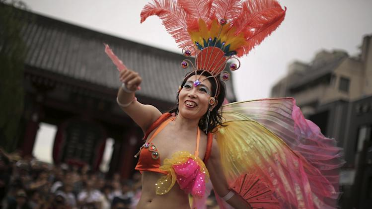 A samba dancer in a colorful costume performs through a street during the annual Asakusa Samba Carnival at Asakusa district in Tokyo Saturday, Aug. 23, 2014. The festival dates back to 1981 and more than 4,700 dancers were on hand for the parade. (AP Photo/Eugene Hoshiko)