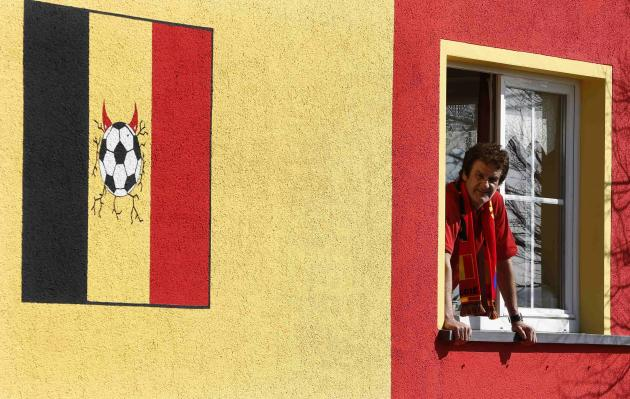 Belgian Wilfried Thelen poses at the window of his house that is painted in the colours of Belgium's national flag in Saint Vith