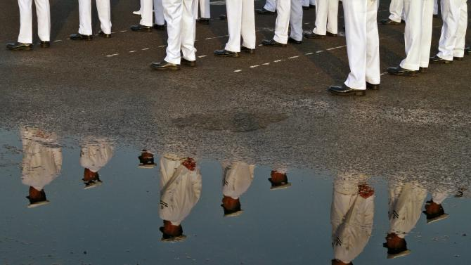 Indian Navy sailors are reflected in a puddle as they take part in the Republic Day parade in Kochi