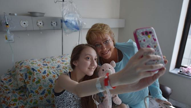 A picture released by the Chilean presidential press office shows President Michele Bachelet posing for a selfie with 14-year-old Valentina Maureira at a hospital in Santiago, on February 28, 2015