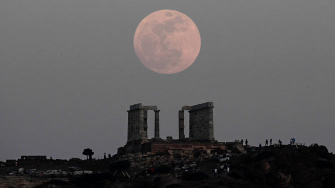 "FILE - In this Saturday, May 5, 2012 file photo, a ""supermoon"" rises behind the Temple of Poseidon in Cape Sounion, Greece, southeast of Athens. The phenomenon occurs when the moon passes closer to Earth than usual. The event on Sunday, June 23, 2013 will make the moon appear 14 percent larger than normal, but the difference is so small that most skywatchers won't notice. (AP Photo/Dimitri Messinis)"