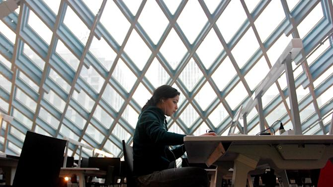 This image taken April 3, 2013 shows a woman working on her laptop at the Seattle Central Library in downtown Seattle. The $165 million building's unusual design and decoration attracts visitors from all over the world. (AP Photo/Manuel Valdes)