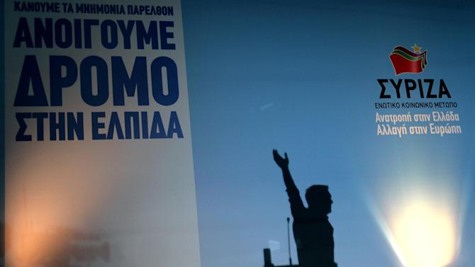 """The shadow of Alexis Tsipras, head of Greece's radical left-wing Syriza party is seen as he waves to his supporters during a rally at Omonia square in Athens, Thursday, June 14, 2012. The background reads """"We open the way for hope,"""" and """"Syriza, reversal in Greece, change in Europe."""" Greece faces crucial national elections on Sunday, that could ultimately determine whether the debt-saddled, recession bound country remains in the eurozone. (AP Photo/Petros Karadjias)"""