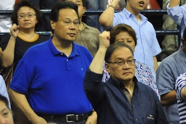 Former CJ Renato Corona and business tycoon Manny V. Pangilinan, are seen during the UAAP Season 75 match between the ADMU Blue Eagles and NU Bulldogs, held at the PhilSports Arena in Pasig city, east of Manila on 13 Sep 2012. (George Calvelo/NPPA Images)