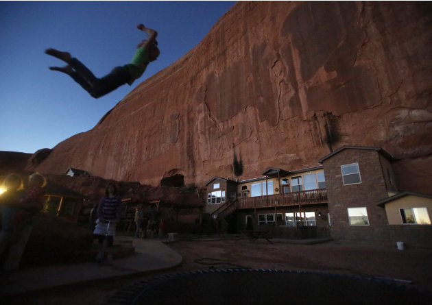 Girls play on a trampoline near a home blasted from a from a rock wall at the Rockland Ranch community outside Moab