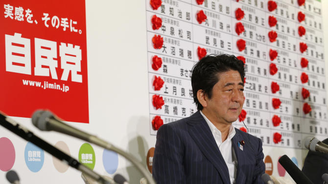 "Japanese Prime Minister Shinzo Abe listens to a reporter's question in front of red rosettes on the names of his Liberal Democratic Party's winning candidates during ballot counting for the upper house elections at the party headquarters in Tokyo Sunday, July 21, 2013. Abe's ruling coalition won a majority in the upper house of Parliament in elections, media projected, giving it control of both chambers and a mandate to press ahead with difficult economic reforms. A sign at left reads: ""Liberal Democratic Party."" (AP Photo/Shizuo Kambayashi)"