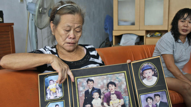 FILE - In this Tuesday, March 25, 2014 file photo, Suwarni, the mother of Sugianto Lo, who was onboard the missing Malaysia Airlines Flight 370 with his wife Vinny, shows her son's family portraits at her residence in Medan, North Sumatra, Indonesia. Indonesians Sugianto Lo and his wife, Vinny Chynthya Tio, were taking a short break away from their three children, their first in more than 17 years as parents. It was hard. Family members had to convince them the children would be fine while they were gone. (AP Photo/Binsar Bakkara, File)