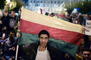 A man holds the flag of the Syrian Kurdish Democratic …