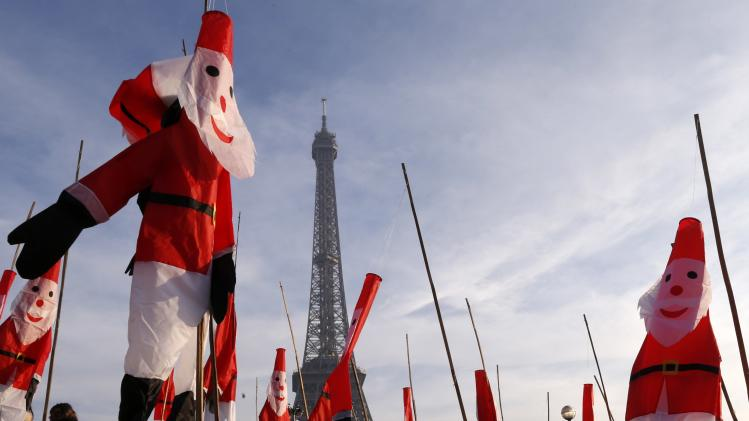 Santa Claus kites float in front of the Eiffel Tower as part of Christmas holiday season preparations in Paris