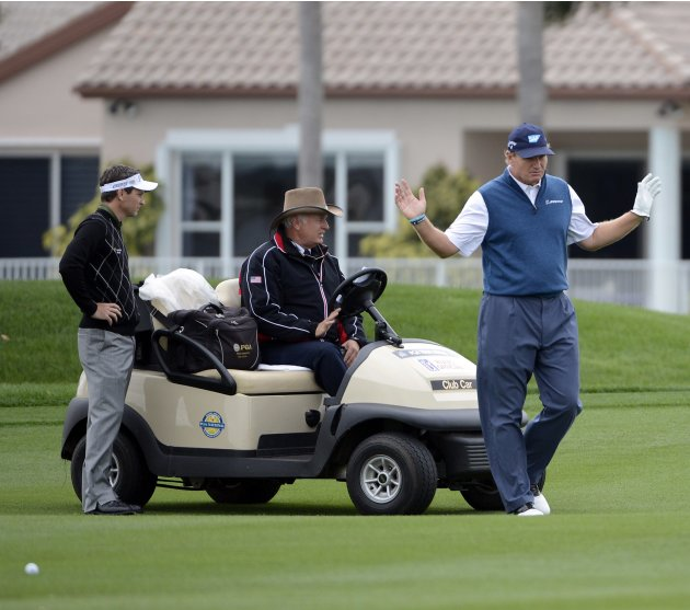 Ernie Els of South Africa gestures as he talks with a PGA Rules Official along with Mark Wilson of the U.S. on the 18th green during second round play in the Honda Classic PGA golf tournament in Palm
