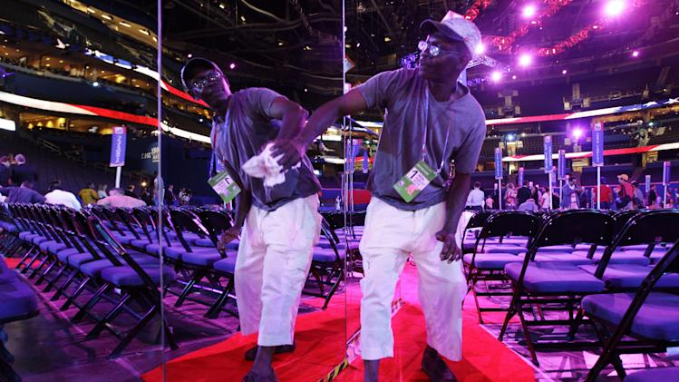 Worker Patrick Gayle of Kissimmee, Fla. wipes the mirror-sided camera stands on the floor of the Republican National Convention in the Tampa Bay Times Forum in Tampa, Fla., on Sunday, Aug. 26, 2012. (AP Photo/Charlie Neibergall)