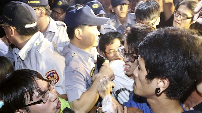 Activists scuffles with police officers during a protest in front of Ministry of Education in Taipei