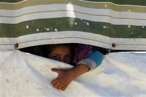 A Palestinian refugee girl from Syria peeps through a tent at Ain al-Helweh Palestinian refugee camp near the port-city of Sidon, southern Lebanon