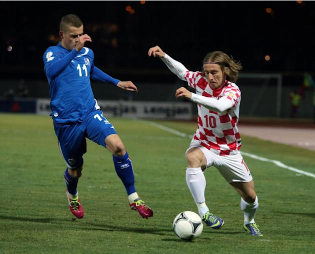 Croatia's Luka Modric, right, controls the ball past Iceland's Alfred Finnbogason during their World Cup qualifying playoff first leg soccer match in Reykjavik, Iceland, Friday Nov. 15, 2013