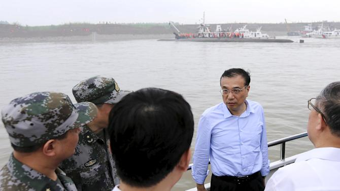 Chinese Premier Li speaks to officers as he inspects the rescue operations of a sunken ship at the Jianli section of the Yangtze River