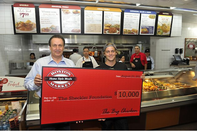 Boston Market CEO George Michel (A.K.A. The Big Chicken) presents a $10,000 check to pro skateboarder Ryan Sheckler at Boston Market during an event to benefit The Sheckler Foundation on Thursday, Aug
