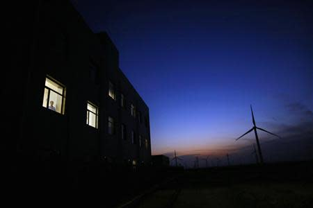 A man stands at the window of a building near a wind turbine used to generate electricity, at a wind farm in Guazhou, 950km northwest of Lanzhou, Gansu Province
