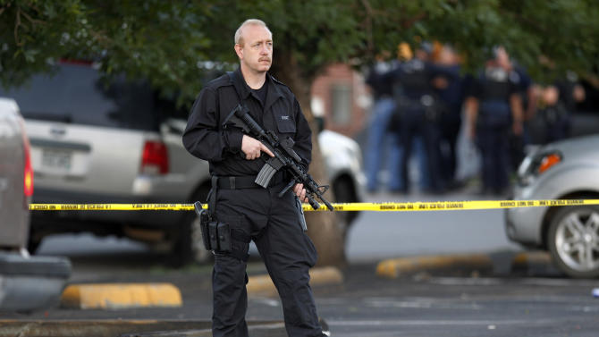 A SWAT team officer stands watch near an apartment house where the suspect in a shooting at a movie theatre lived in Aurora, Colo., Friday, July 20, 2012. As many as 14 people were killed and 50 injured at a shooting at the Century 16 movie theatre early Friday during the showing of the latest Batman movie. (AP Photo/Ed Andrieski)