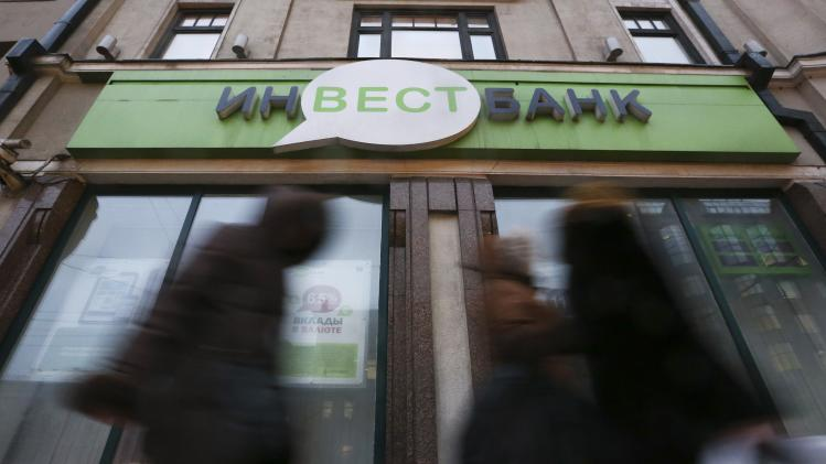 People pass by an office of Investbank in Moscow