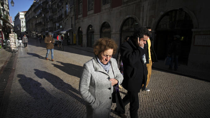 People walk along a pedestrian street in downtown Lisbon, Monday, Jan. 14, 2013. The Portuguese center-right coalition government has been implementing a tough packet of economic measures, that includes a significant tax increase, linked to a euro 78 billion ($100 billion) international bailout needed in 2011. (AP Photo/Francisco Seco)