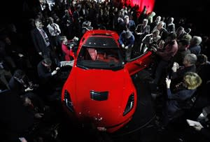 Journalists surround General Motors new 2014 Chevrolet Corvette Stingray, Sunday, Jan. 13, 2013, the night before press days at the North American International Auto Show in Detroit. When 1,000 GM engineers and designers started work on the next-generation Corvette, they began with the usual priority list for a muscle car. Killer looks. Big engine. Fast. But topping the list was something that belies the roar of the Chevrolet's giant V-8: Gas mileage. (AP Photo/Paul Sancya)