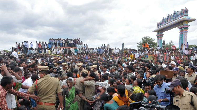 Relatives wail as people crowd at the site of a collision between a train and a school bus in Medak
