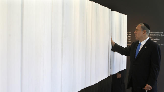 """Israeli Prime Minister Benjamin Netanyahu looks at """"The Book of Names"""", which contains the names of 4.2 million Jews killed during the Holocaust, at the opening of a new pavilion at the former Nazi German death camp of Auschwitz, in Oswiecim, Poland, Thursday, June 13, 2013. The exhibition in Bloc 27 was curated by Israel's Yad Vashem Institute Chairman Avner Shalev. It is meant to educate visitors about the Holocaust and the Nazi Germany's quest to exterminate the Jewish people. The event closed Netanyahu's two-day visit to Poland that was steeped in symbolism, as it focused on the Jewish people's painful history there during World War II as well as on the strong relations between Poland and the Jewish state today. (AP Photo/Czarek Sokolowski)"""