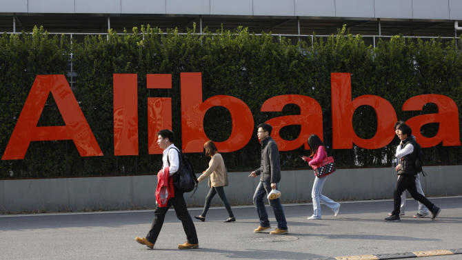 FILE - In this March 17, 2014 file photo, people walk past a company logo at the headquarters of Alibaba Group in Hangzhou, in eastern China's Zhejiang province. The Monster Tron T1 headphones sold on Chinese e-commerce giant Alibaba's Taobao site are a tempting offer for audiophiles looking for a good price on authentic state-of-the-art hi-fi equipment but the California company, best known for its audio-visual cables, said Monday, May 27, 2014 that 99.5 percent of purported Monster products sold on Alibaba sites are fakes, based on thousands of listings the company's investigators have examined over the years. (AP Photo) CHINA OUT