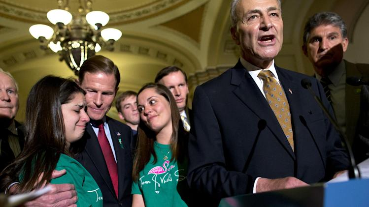 Sen. Chuck Schumer, D-N.Y., right, speaks as Sen. Richard Blumenthal, D-Conn., third from left, hugs Carlee Soto, sister of Sandy Hook teacher Victoria Soto, second from left, and Erica Laffferty, daughter of Sandy Hook principal Dawn Hochsprung, after a vote on gun legislation on Capitol Hill on Wednesday, April 17, 2013, in Washington. Senate Republicans backed by a small band of rural-state Democrats scuttled the most far reaching gun control legislation in two decades, rejecting calls to tighten background checks on firearms buyers. (AP Photo/Evan Vucci)