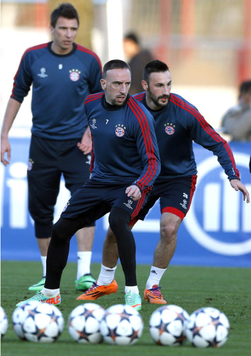 Bayern's Franck Ribery of France, foreground left, Diego Contento, right, and Bayern's Mario Mandzukic of Croatia, background, challenge for the ball during a training session in Munich, south