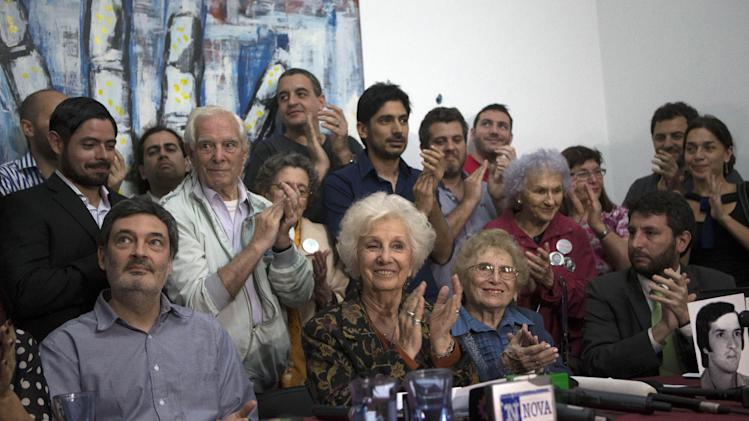 Human right activists react as Estela de Carlotto, center, president of the Grandmothers of Plaza de Mayo, Argentina's leading human rights group, applauds after announcing that tests have identified the granddaughter of one of the group's late founders Alicia Zubasnabar de la Cuadra, In Buenos Aires, Argentina, Friday, Aug. 22, 2014. Zubasnabar de la Cuadra the group's first president, died in 2008, her daughter gave birth while a prisoner of the 1976-83 military dictatorship and hasn't been seen since. (AP Poto/Eduardo Di Baia)