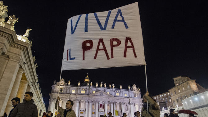 """Faithful hold up a sign with the writing in Italian reading """"Hail to the Pope"""" after the election of Pope Francis, the 266th pontiff of the Roman Catholic Church, in St. Peter's Square at the Vatican, Wednesday, March 13, 2013. Cardinal Jorge Bergoglio of Argentina was elected pope. (AP Photo/Angelo Carconi)"""