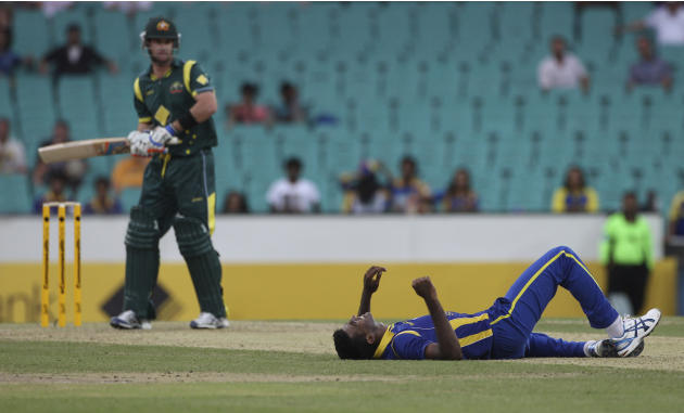 Sri Lanka cricket player Farveez Maharoof, right, lies on the pitch after missing a catch hit by Australia's Daniel Christian during a ODI cricket match against Australia at the Sydney Cricket Ground