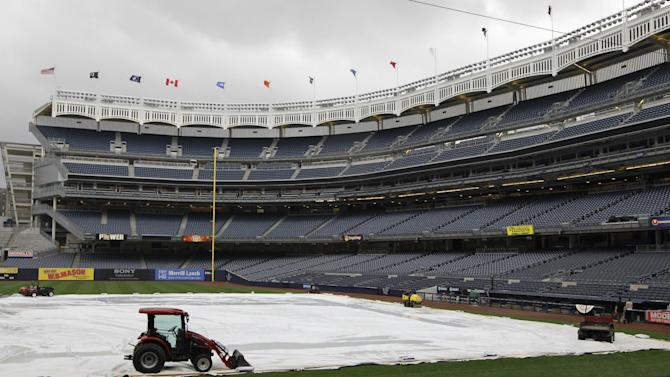 A tractor and other equipment stand on the tarp to prevent it from blowing away in high winds after Tuesday night's baseball game between the New York Yankees and the Toronto Blue Jays was postponed because of inclement weather, at Yankee Stadium in New York, Sept. 18, 2012. (AP Photo/Kathy Willens)