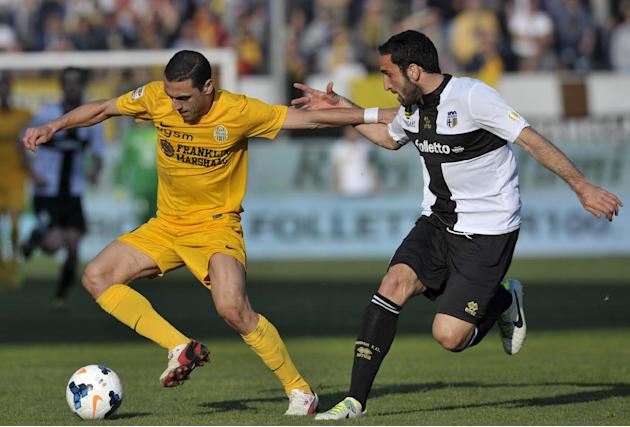 Parma's Cristian Molinaro, right, vies for the ball with Verona's Caldeira Romulo of Brazil, during their Serie A soccer match at Parma's Tardini stadium, Italy, Sunday, March 9, 2014