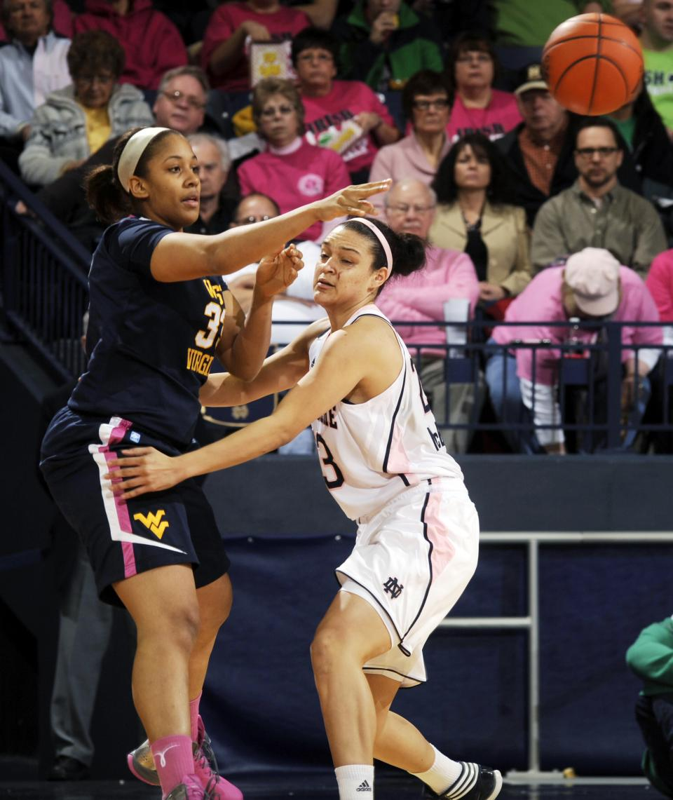 West Virginia center Ayana Dunning, left, throws a pass around Notre Dame guard Kayla McBride during the first half of an NCAA college basketball game, Sunday, Feb. 12, 2012, in South Bend, Ind. (AP Photo/Joe Raymond)
