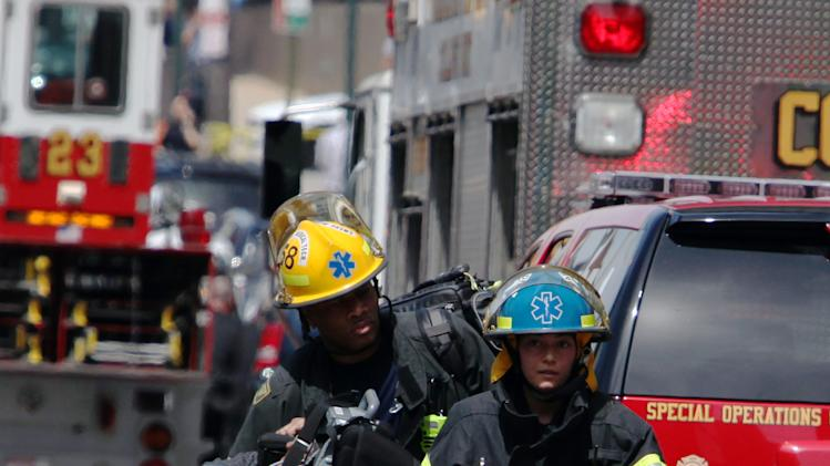 Rescue personnel evacuate an injured person from the scene of a building collapse in downtown Philadelphia Wednesday, June 5, 2013.  A four-story building being demolished collapsed Wednesday on the edge of downtown, injuring 12 people and trapping two others, the fire commissioner said.   (AP Photo/Jacqueline Larma)