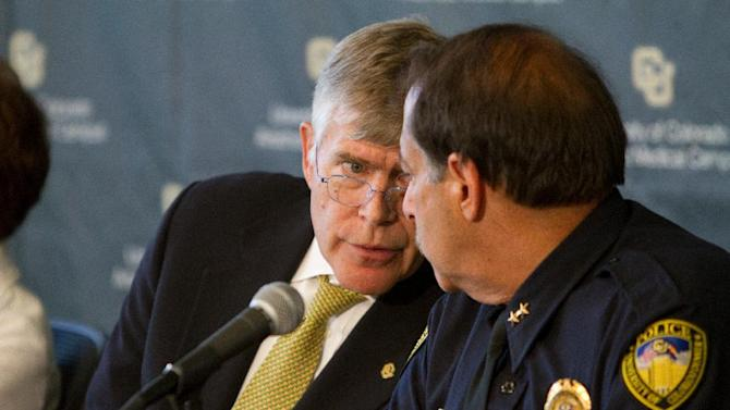 University of Colorado-Denver Chancellor Don Elliman, left, leans over to speak with Doug Abraham, Chief of Police for the University of Colorado, during a news conference Monday, July 23, 2012, in Aurora, Colo. The conference was called to discuss the program, procedure and policy that surround the Neuroscience program that James Holmes was recently enrolled in before allegedly killing 12 and injuring dozens of others in a shooting at an Aurora, Colo. movie theater last Friday. University officials won't say whether they saw any signs of academic or behavioral trouble in Holmes. (AP Photo/Barry Gutierrez)